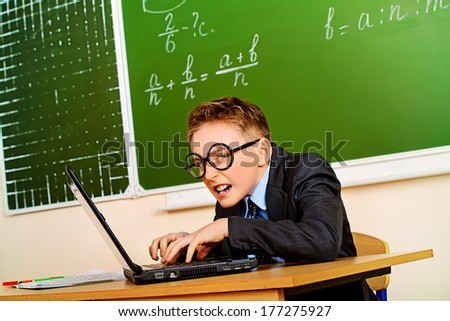 Funny schoolboy in a suit working on a laptop at school. Education. - stock photo