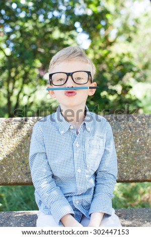 funny schoolboy playing with pencil and being silly ready for school enjoying warm weather in the park - stock photo