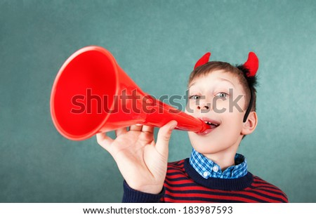 Funny schoolboy pretending to be the devil with horn playing red pipe smiling. Behavior concept - stock photo