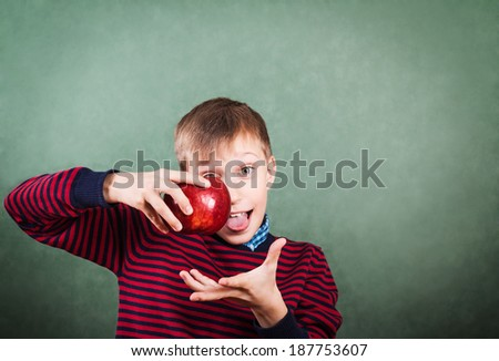 Funny schoolboy standing over a blackboard holding a big red apple showing his tongue   - stock photo