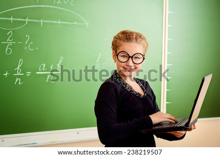 Funny schoolgirl in big round glasses holding her laptop and smiling at the camera. Education. - stock photo