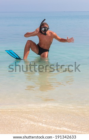 Funny scuba diver having fun at the beach - stock photo