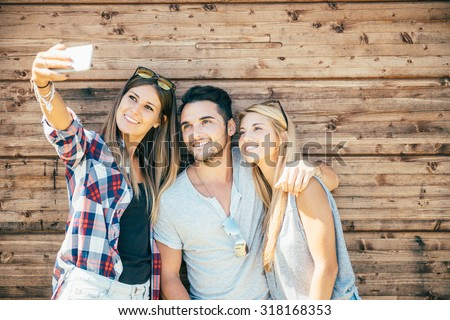 Funny selfie with friends. three cheerful young people making selfie and smiling while standing outdoors. wooden background - stock photo