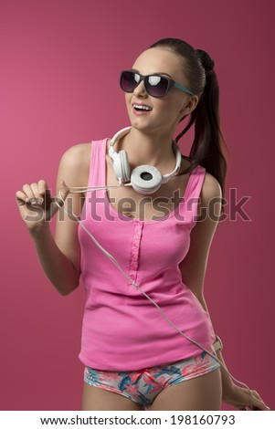 funny sexy girl with pink singlet, panties and sunglasses listening music with headphones  - stock photo