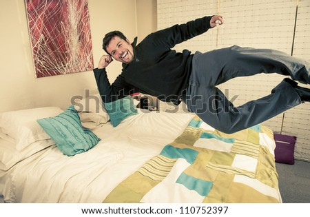 Funny shot of a man smiling and levitating over his bed. - stock photo