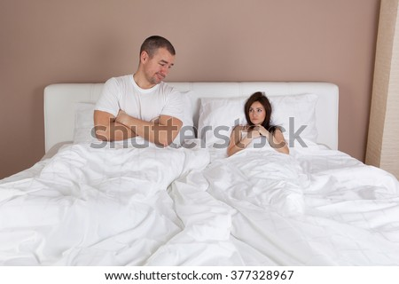 Funny situation in bed. Young couple lying in bed and woman is very small - stock photo