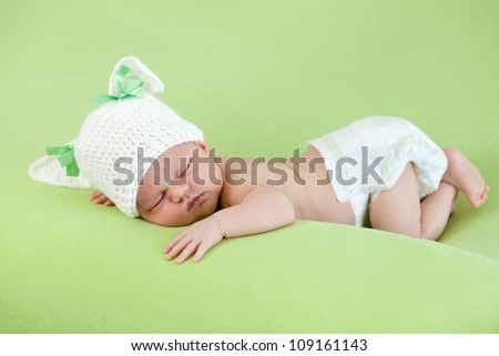Funny sleeping newborn baby. Bunny cap on head of girl. - stock photo