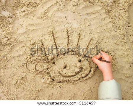 Funny smiley drawn by child's hand on wet sand - stock photo
