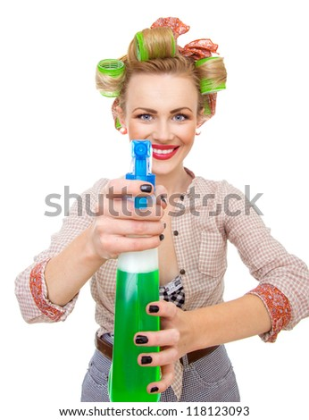 Funny smiling housewife / woman spraying the cleaner on you, isolated on white. Glass or window cleaner - stock photo