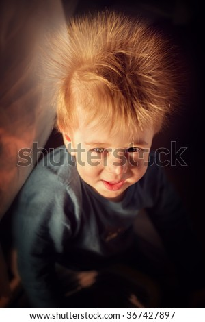 Funny smiling red haired little boy with electrified hair like big dandelion. Image with selective focus and toning - stock photo