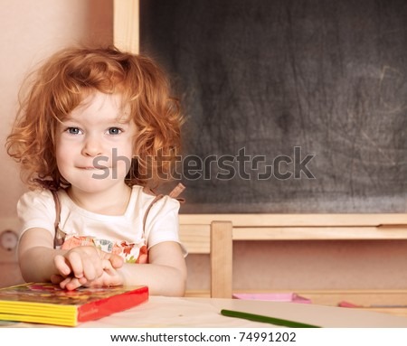 Funny smiling schoolchild in a class against blackboard - stock photo
