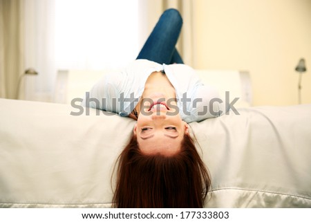 Funny smiling woman lying on the bed at home - stock photo