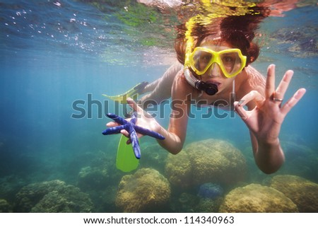 funny snorkeler showing gorgeous starfish - stock photo