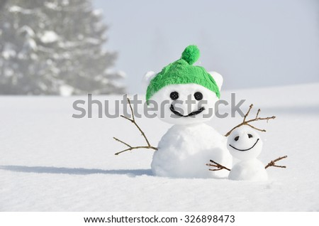 Funny snowmen against Swiss Alps - stock photo