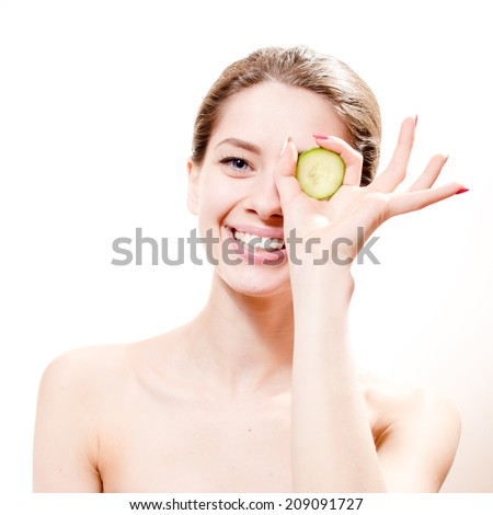 funny spa: young beautiful woman standing with slice of cucumber in the hand one piece on eye isolated on white background, portrait - stock photo