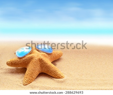 Funny starfish with sunglass on the summer beach at ocean background - stock photo