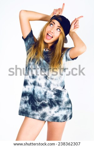 Funny studio portrait of young cheeky pretty woman having fun and showing  horns, wearing stylish swag hat and vintage grey dress.  - stock photo