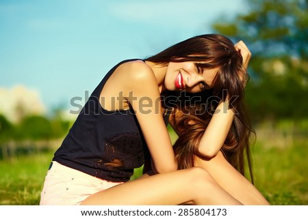 Funny  stylish sexy smiling beautiful sunbathed young woman model in summer bright  hipster cloth sitting  in the park on grass - stock photo