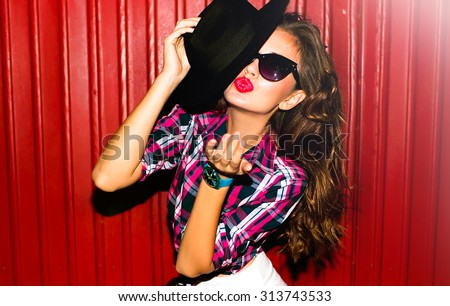 Funny stylish sexy smiling beautiful young hippie woman model in summer white fresh hipster clothes sitting in the street,bright colored clothes,street fashion,send kiss,red lips,black hat and glasses - stock photo