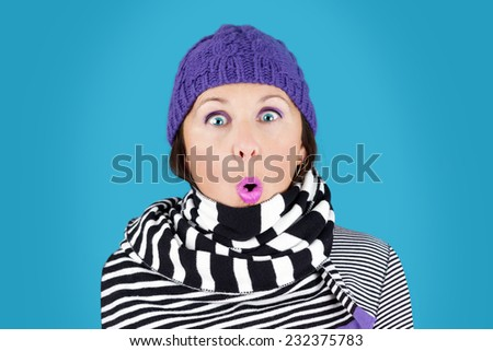 Funny surprised face woman with wool hat and stripe black and white scarf: humorous winter concept - stock photo