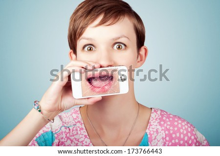 Funny technology portrait of a stressed woman expressing open mouth dismay on the shattered screen of her broken mobile phone  - stock photo