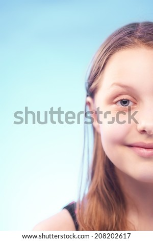 Funny teen girl grimacing. Half of the face - stock photo