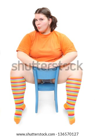 Funny teenage girl sitting on a blue chair. - stock photo