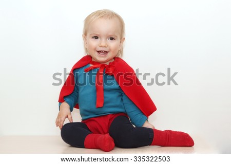 Funny toddler (boy) dressed as a superhero over white background, indoor portrait, superhero concept - stock photo
