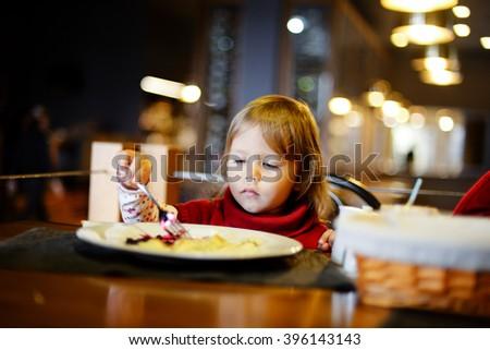 funny toddler girl eating in the restaurant - stock photo