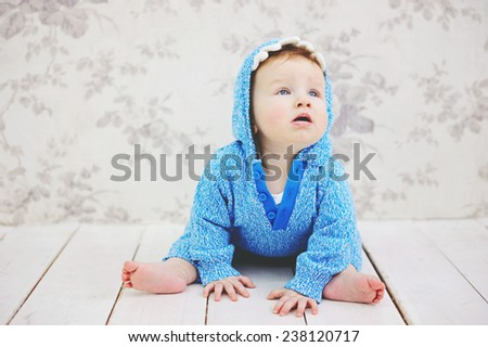 Funny toddler girl in a blue sweater sitting on the white floor  - stock photo