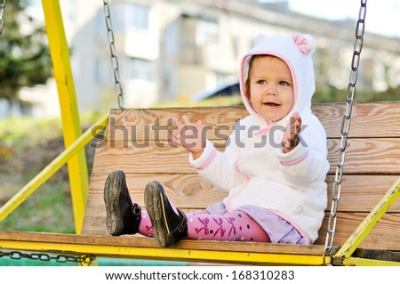 funny toddler girl on swing - stock photo