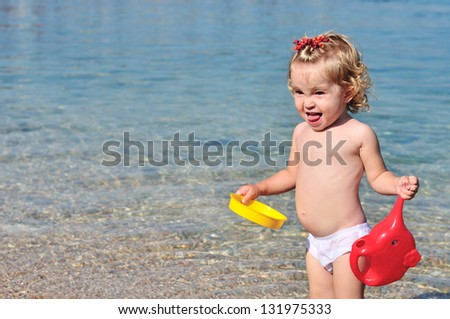 funny  toddler girl on the beach in sea water - stock photo