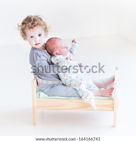 Funny toddler girl playing with her newborn baby brother in a toy bed - stock photo