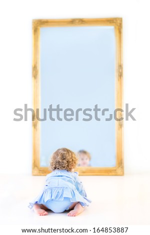 Funny toddler girl with beautiful curly hair wearing a blue dress watching her reflection in a mirror - stock photo