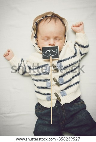 Funny toned portrait of little baby boy lying on bed with decorative mustaches - stock photo