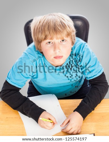 funny top view of a young boy doing homework - stock photo