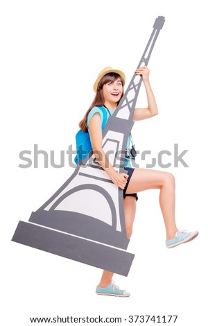 Funny travel concept. Full length studio portrait of happy pretty young woman stealing maquette of Eifel tower. Isolated on white. - stock photo