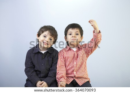 Funny twins are enjoying the day together in front of a blue background while they should be ready to go to the school. - stock photo