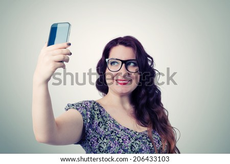 Funny viper girl photographs himself on smartphone - stock photo