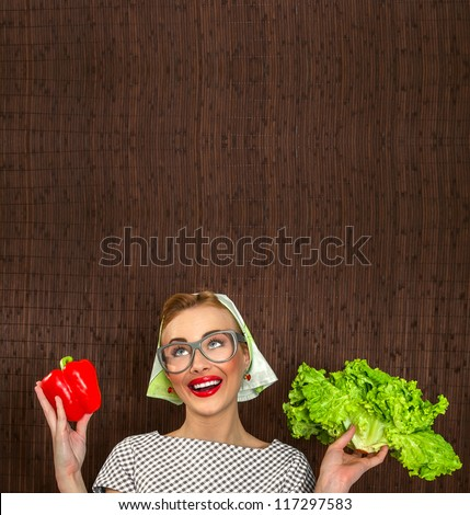 Funny woman cook holding salad and sweet pepper, space for yuor text - stock photo