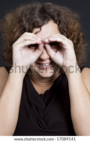 funny woman following the target over dark background - stock photo