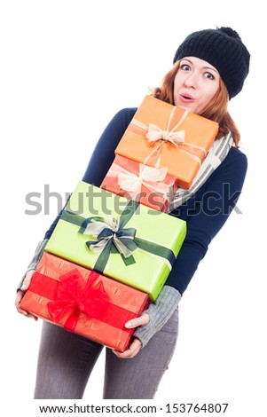 Funny woman in winter clothes holding many presents, isolated on white background. - stock photo