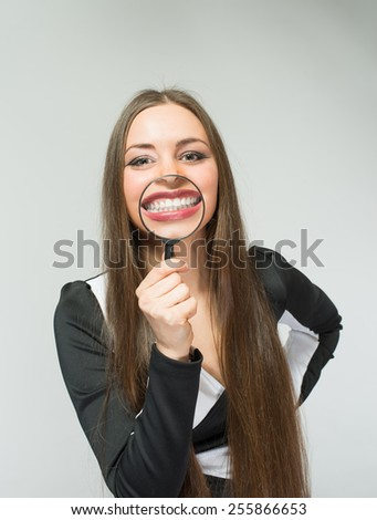 funny woman smiling and show teeth through a magnifying glass over white background - stock photo