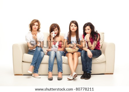 funny women sitting on couch watching sad movie depressed - stock photo