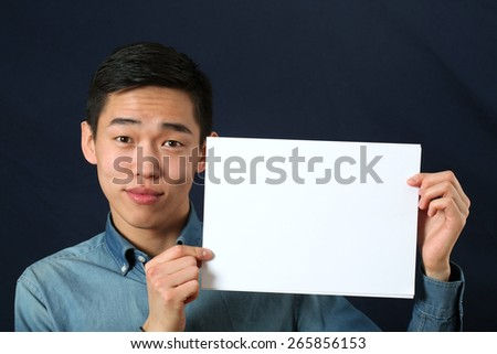 Funny young Asian man showing copy space page and looking at camera - stock photo