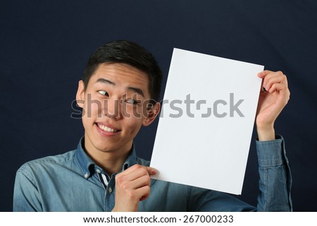 Funny young Asian man showing white copy space page and looking sideways - stock photo