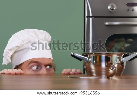Funny young chef strange looking at pot - stock photo