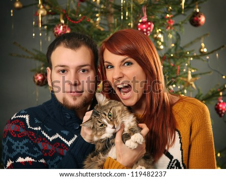 funny young couple and christmas tree - stock photo