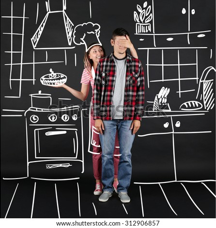 Funny young couple at the kitchen, on black background - stock photo
