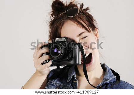 Funny young girl with photo camera with moving, blowing hair. - stock photo